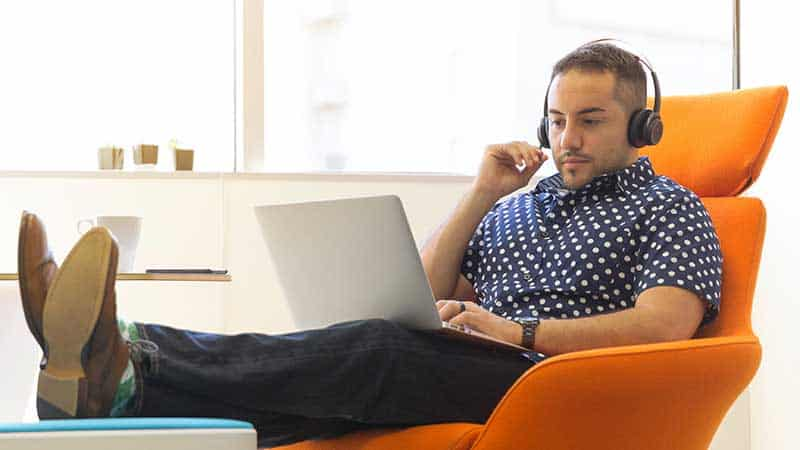 man with earphones and laptop